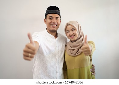 muslim couple showing thumb up over white wall