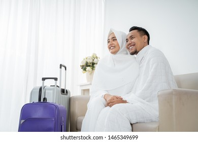 muslim couple sit wearing white traditional clothes for Ihram before umrah with luggage