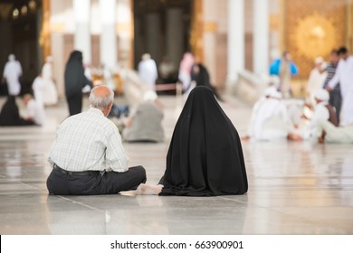 Muslim couple sitting in front of Medina mosque