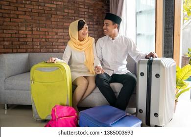 muslim couple with suitcase and backpack. family travelling eid mubarak mudik tradition