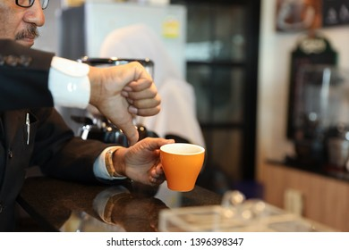 muslim customer businessman wearing black suit thumb down to a cup of coffee and complain at counter with young muslim barista businesswoman