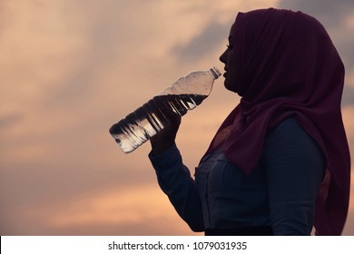 Muslim drinking water at sunset