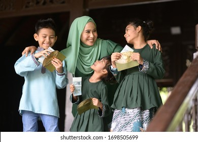 Muslim family, children received money packet as blessing, Hari Raya Eid Al-Fitr concept.