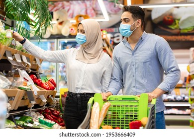 Muslim Family Couple Doing Grocery Shopping Wearing Protective Face Masks Buying Food Together In Modern Supermarket. Islamic Husband And Wife Choosing Fresh Organic Vegetables In Hypermarket