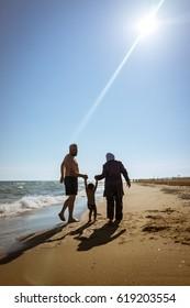 Muslim family, dad and mom with burkini on the beach walking near sea