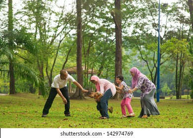 Muslim family having fun at green outdoor park. Beautiful Southeast Asian family playing together.