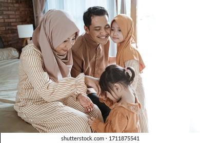 muslim family and kid greeting and asking forgiveness shaking hand on ramadan and eid mubarak