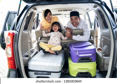 muslim family with kid sitting in the car trunk with suitcase. eid mubarak or idul fitri mudik