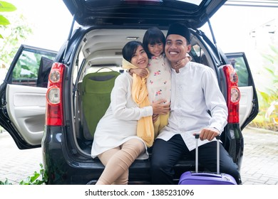 muslim family with kid sitting in the car trunk with suitcase. eid mubarak or idul fitri mudik
