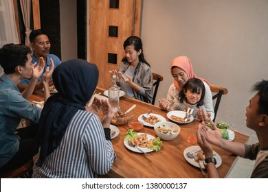muslim family pray before having their dinner together at home