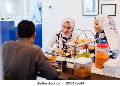 A Muslim family sits down for a meal at home. Two women in head scarves and a man enjoy a quiet repast.