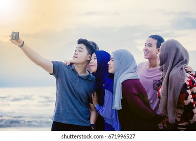 Muslim family taking selfie outdoors with backlight contrast Happy friendship concept with young people having fun together Vintage filtered look with marsala color tones and sunshine halo flare.