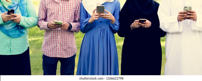 Muslim family using smartphone outdoors