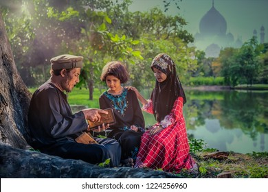 Muslim father as parent reading Islam holy book, Al Quran, to his children under tree with background of mosque across lake
