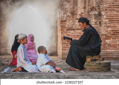 Muslim father as parent reading Islam holy book, Al Quran, to his children and son in old mosque