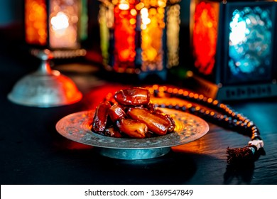The Muslim feast of the holy month of Ramadan Kareem with dates on a tray on a dark background. Beautiful background with a shining lantern Fanus.