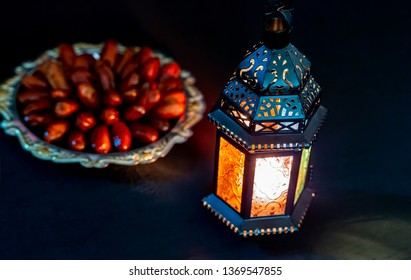 The Muslim feast of the holy month of Ramadan Kareem with dates on a tray on a dark background. Beautiful background with a shining lantern Fanus. Free space for your text.