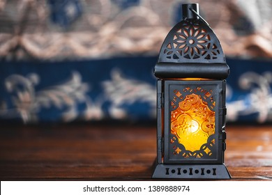 The Muslim feast of the holy month of Ramadan Kareem. Beautiful background with a shining Moroccan lantern on wooden table with the carpet. Free space for your text