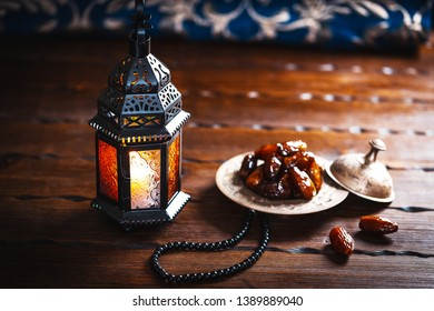 The Muslim feast of the holy month of Ramadan Kareem. Beautiful background with a shining Moroccan lantern and dried dates on wooden table with the carpet. Free space for your text