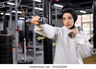 muslim female boxer in hijab white sportswear standing in fighter pose with dumbbells, young arabic woman doing exercises, leading healthy lifestyle. sport in Islamic countries, women rights concepts