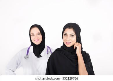 Muslim female doctor with arabic female patient on white background