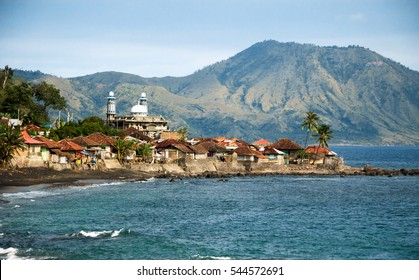 Muslim fisherman village with mosque and volcano at the background. Near Ende, Flores Island, Indonesia.
