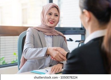 Muslim foreign manager deal with office lady. They have a good partnership. They are shaking hands in the office.