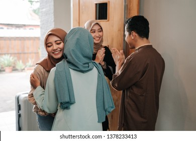 muslim friend and family visiting home and greet embrace each other celebrating eid mubarak