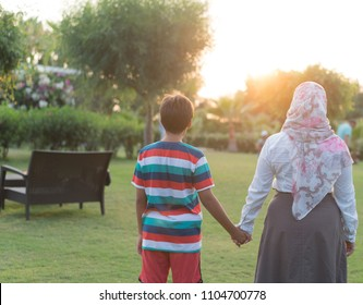 Muslim girl and boy on meadow in beach park