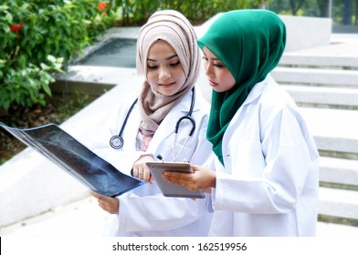 Muslim girl doctor look result x-ray with tablet