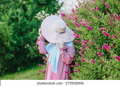 Muslim girl with a hat on a background of pink flowers. Islam. Muslim woman in a pink dress and a hollow hijab. Modern muslim woman.