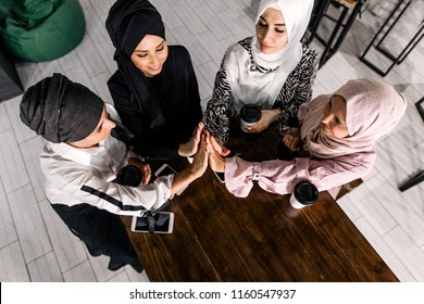 Muslim girl hijab communicate in social networks via phone on background of friends in a cafe, the view from the top