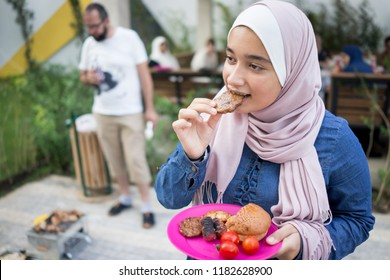 Muslim girl with hijab eating barbecue food