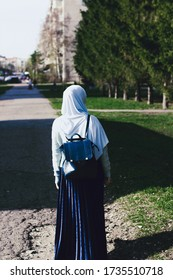 Muslim girl in a hijab walks in the park among the trees. Muslim female student with a blue backpack. Education in Muslim countries. Muslim woman in a blue shawl. Study