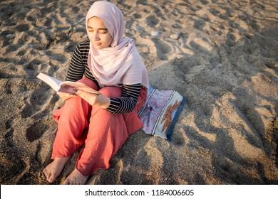 Muslim girl reading book on beach