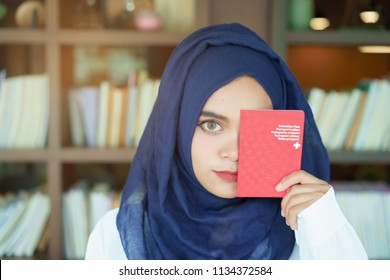 muslim girl showing a swiss passport book with a happy face.