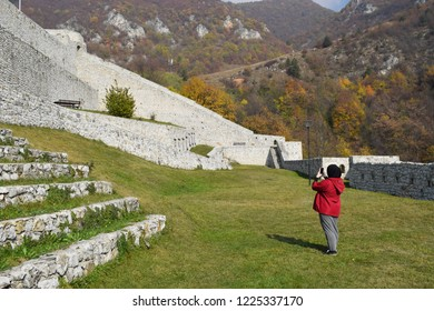 Muslim girl tourist photographing beauty of ancient fortress in Travnik,Bosnia nad Herzegovina during autumn time