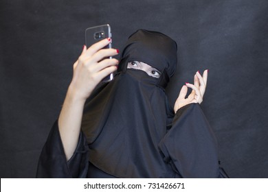 Muslim girl wearing a burka and having a selfie on smart phone