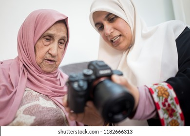 Muslim grandmother with daughter watching pictures on camera