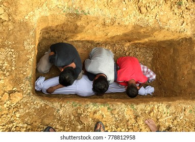 Muslim gravediggers preparing graveyard.