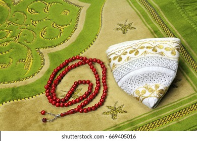 Muslim hat and rosary beads on a prayer rug.
