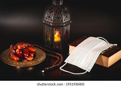 Muslim holiday of the holy month of Ramadan Karim on a dark background with shining lantern and a book Koran with medical mask. Celebrating Holy month Ramadan in quarantine. Epidemic, coronavirus