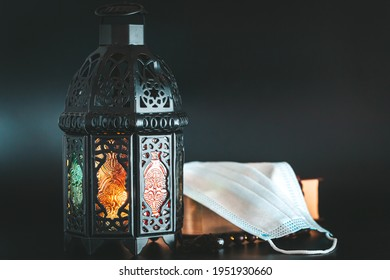 Muslim holiday of the holy month of Ramadan Karim on a dark background with shining lantern and a book Koran with medical mask. Celebrating Holy month Ramadan in quarantine.