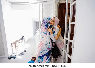 A Muslim husband and wife couple greet a guest at their door and invite her in to celebrate Hari Raya, a Muslim celebration of love and forgiveness. The two women are hugging joyously as they meet.