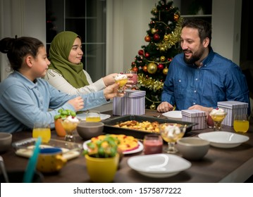 Muslim interreligious family with christmas tree in background