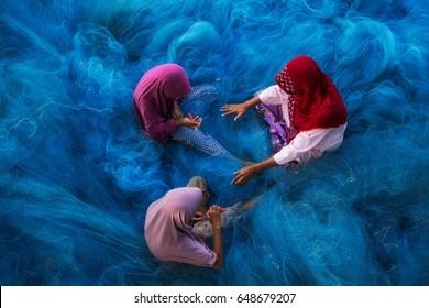Muslim or Islam woman are repairing blue fishing net