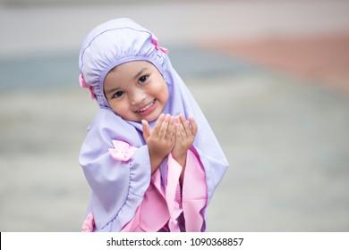 Muslim kid girl wearing Hijab praying Dua during Ramadan period. The concept is Islam,Dua,religion,worship and sin.