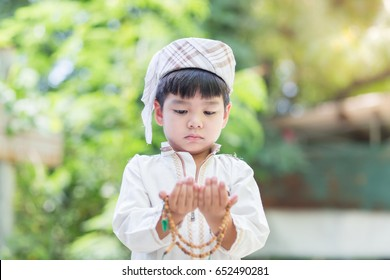Muslim kid praying - islam boy series of related photos showing the entire prayer on green background.islam asian. Ramadan Portrait.