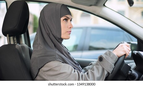 Muslim lady sitting in car looking rear view mirror, driving license, transport