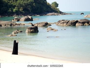 Muslim lady walking on the beach